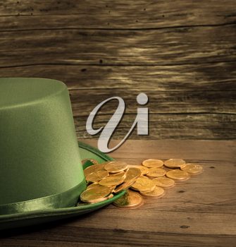 Treasure of pure gold coins inside the rim of a green velvet hat. Placed on wooden table to celebrate luck on St Patrick's Day on March 17th