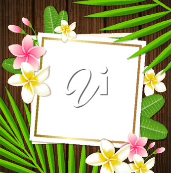 Decorative floral frame with tropical flowers and palm leaves on a wooden background
