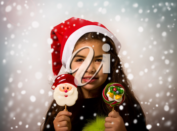 A little girl in a Santa Claus hat holds bright New Year candies in snowflakes
