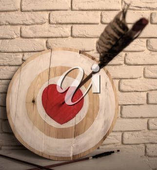 Handmade rough wooden target with a center in the form of a red heart and an arrow from a bow that hit the center and two arrows missed.