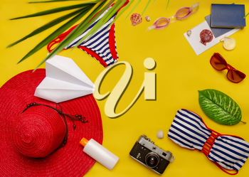 top view set of women's beach accessories and things for relaxation on a bright yellow background