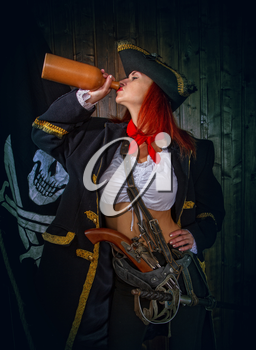 Young Attractive Armed Girl Pirate Captain Drinks Clay Bottle Alcohol Jolly Roger Flag Background