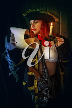 Young Attractive armed girl pirate captain examines a map by candlelight against the background of the flag Jolly Roger