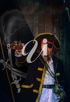 Adult pirate captain in a traditional costume shoots a pistol and holds a sword in his hands against the background of a jolly roger