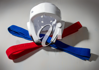 White protective light helmet for karate do, and red and blue belts for competitions