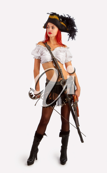 sexy girl in a pirate costume and a cocked hat stands armed with a gun and a sword on a white background