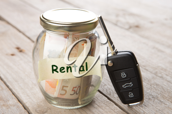Car rent concept - money glass , car key and roadmap