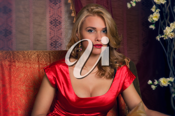 Portrait of the beautiful woman in a red east interior