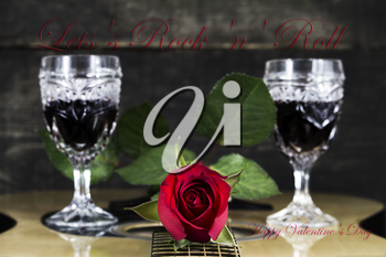 Red Rose and Wine Glasses Resting On Acoustic Guitar With Sign Lets Rock And Roll. Valentine's day concept