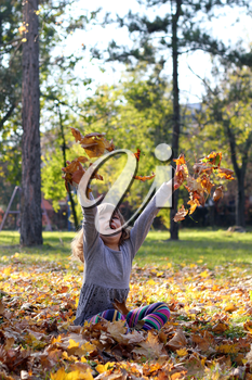 happy little girl throws leaves in autumn park