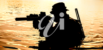 Silhouette of special forces with rifle in action during raid crossing river in the jungle waist deep in the water