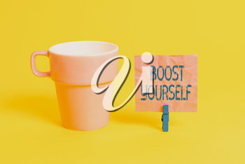 Text sign showing Boost Yourself. Business photo showcasing to make yourelf feel more positive or more confident Cup empty paper blue clothespin rectangle shaped reminder yellow office
