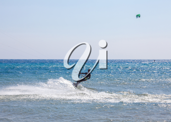 A man in full gear suit above the ocean. The athlete holding firm the handle while gliding in the sea. Ski boarding in action. Water sports ideas and beach activities