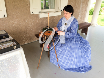 lady in period costume makes human hair jewelry horse hair