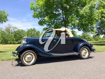 1934 Ford Roadster blue in park on green grass outdoor sky