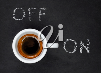 Top view of a Espresso Coffee in small white cup with a lettering ON and OF on black slate background
