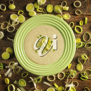 Top view of a bowl of leek soup surrounded by leek rings